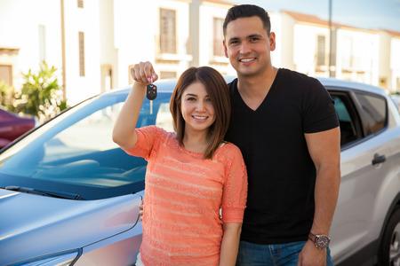 Muchacha bonita y su marido mostrando sus llaves del coche para su coche nuevo
