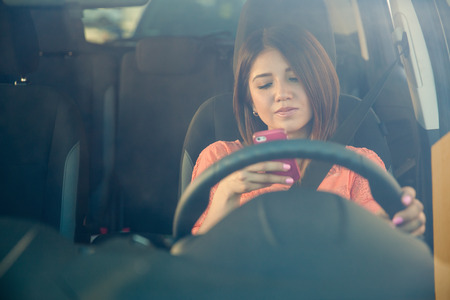 driving a car: Portrait of a young woman texting on her smartphone while driving a car