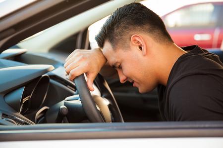 un homme triste: Vue de profil d'un jeune homme appuy� sur le volant et se sentir stress� et boulevers� Banque d'images