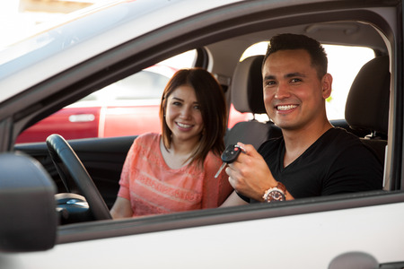 Portrait of a Hispanic young couple excited and ready to ride their new car Stockfoto