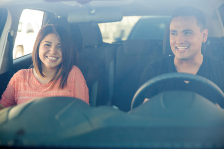 Portrait of a cute Hispanic couple having fun in a car, seen through the windshield