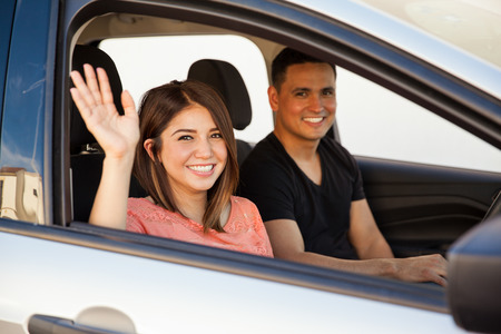 Attractive young couple saying goodbye before driving away in their car photo