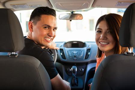 hombre conduciendo: Vista trasera de una pareja de hispanos lindo que viajan en coche y sonriente Foto de archivo