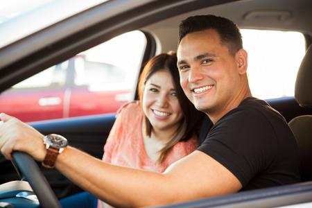 hombre manejando: Retrato de una atractiva pareja de hispanos que conduce un coche ya punto de ir en un viaje Foto de archivo