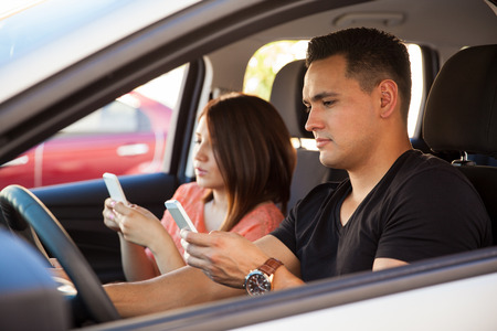 Portrait of reckless young adults texting on their smartphones and driving, ignoring the road Imagens