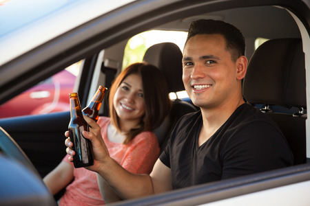 drinking driving: Portrait of a couple of reckless young adults drinking beer and driving Stock Photo