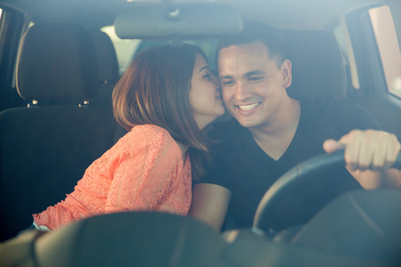 street love: Beautiful young woman kissing her boyfriend in the cheek while he drives. Shot through the windshield