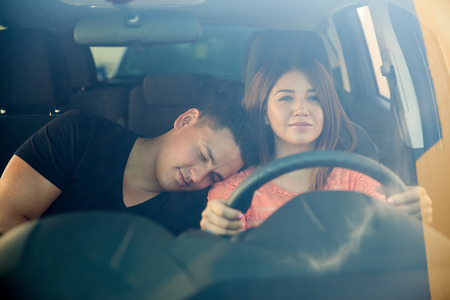 sleep: Portrait of a beautiful young woman driving a car while her boyfriend falls asleep on her shoulder