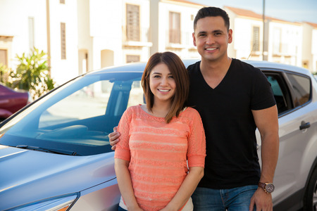 Portret van een mooi Latijnse paar die naast hun nieuwe auto staat en lacht