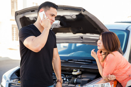 llamando: Apuesto joven que usa su teléfono para pedir un poco de ayuda de ruta para su coche Foto de archivo