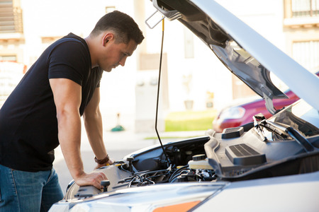 cars road: Profile view of a handsome young Hispanic man looking at a car with its hood open, trying to fix it Stock Photo