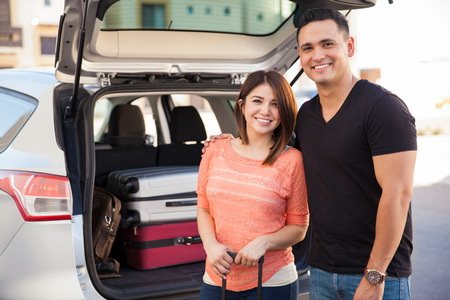 Cute Hispanic couple loading luggage to a car before going on a road trip