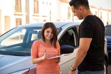Happy young Hispanic woman signing a financing plan for buying her brand new car