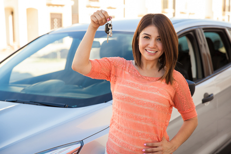 brand new: Beautiful young brunette showing off the keys for her brand new car and smiling