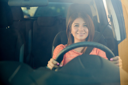 Cute young brunette enjoying a car ride and smiling, shot through the windshield Standard-Bild