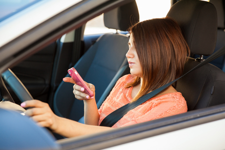 reckless: Reckless young brunette using a smartphone while driving a car