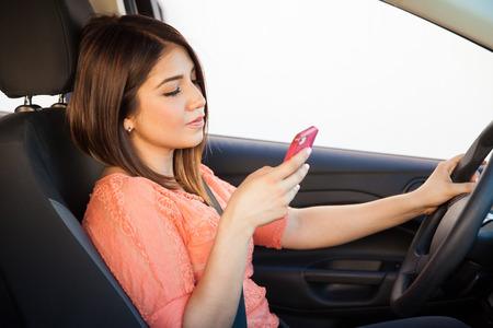 manejando: Vista de perfil de una mujer joven latina imprudente usando un tel�fono inteligente mientras conduce Foto de archivo