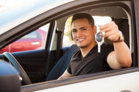 hispanic: Attractive young Hispanic man showing his new car keys and smiling