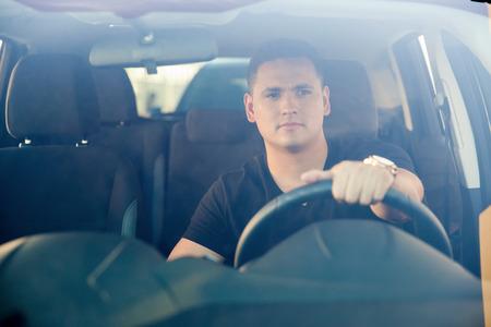 Портрет симпатичного молодого человека за рулем своего автомобиля, выстрелил через лобовое стекло