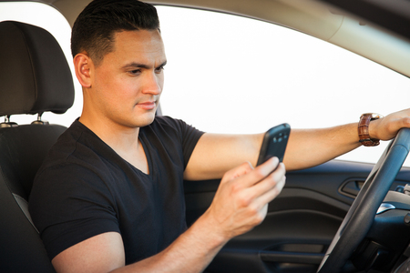 reckless: Profile view of a young man looking at his smartphone while he drives a car