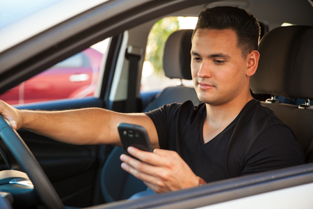 reckless: Portrait of a young reckless male driver using his cell phone behind the wheel