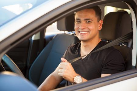 cinturón de seguridad: Retrato de un joven hispano feliz poniendo su cinturón de seguridad
