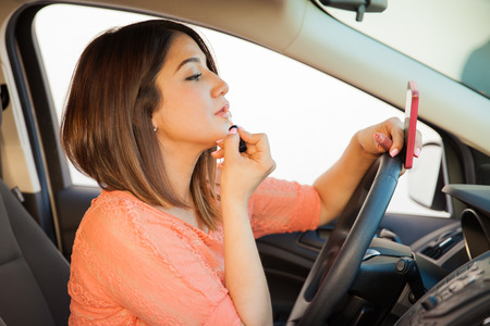 sms: Profile view of a young brunette putting some lipstick on and looking at her cell phone while driving a car