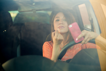 Portrait of a distracted young woman looking at her smartphone and putting some lipstick on while driving a car Foto de archivo