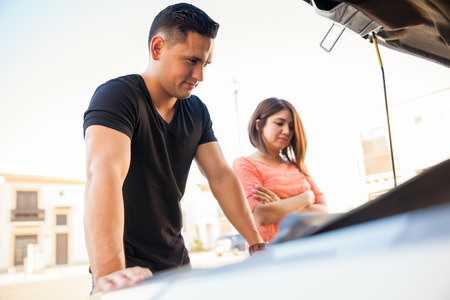 car trouble: Portrait of a young Hispanic couple having some car trouble on a sunny day Stock Photo