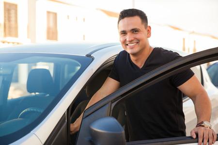 Portrait d'un beau jeune hispanique entrer dans sa voiture et souriant
