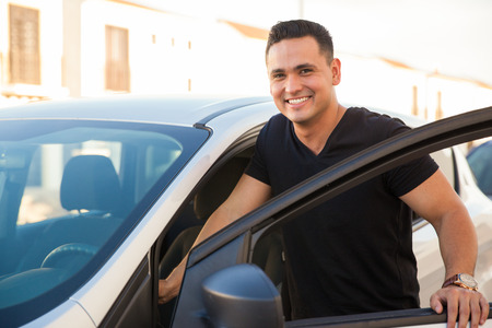 cars on the road: Portrait of a Hispanic young handsome man getting into his car and smiling Stock Photo