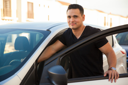 car door: Attractive young man standing next to his car and about to get in
