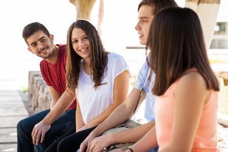 Porträt einer schönen curly Brünette Blickkontakt während hanging out mit ihren Freunden