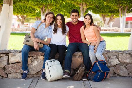 amigos abrazandose: Retrato de cuerpo entero de un grupo de estudiantes universitarios hispanos relajante en la escuela