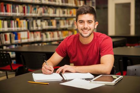 estudiantes: Atractivo estudiante universitario masculino haciendo un poco de tarea en la biblioteca de la escuela y sonriente Foto de archivo