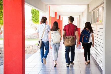 学校の廊下を歩いて離れて大学生のグループの後姿 写真素材