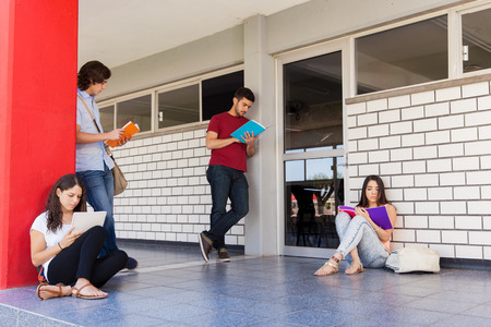 Bunch of college students waiting in the hallway outside a classroom and studying before a test Stok Fotoğraf