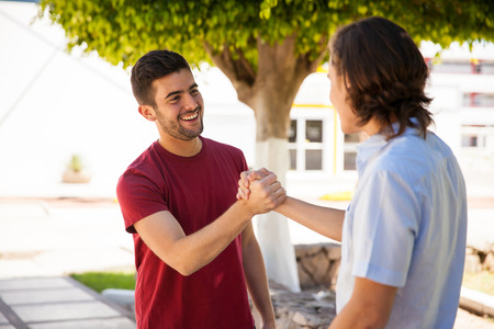 Pair of male friends greeting each other with a handshake at school Foto de archivo