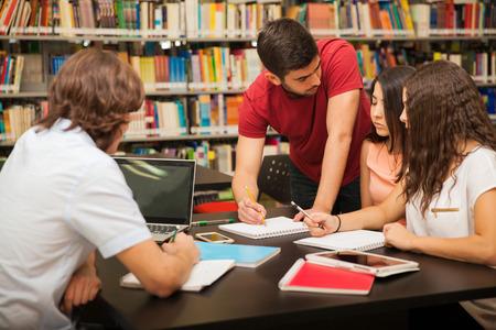 colegios: Estudiante universitario de sexo masculino que explica algo de trabajo escolar para sus colegas, mientras estudiaba en la biblioteca Foto de archivo