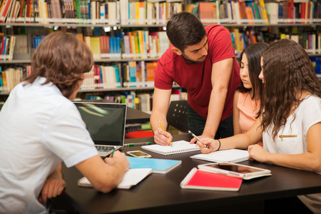 Male college student explaining some school work to his colleagues while studying in the library Stock Photo