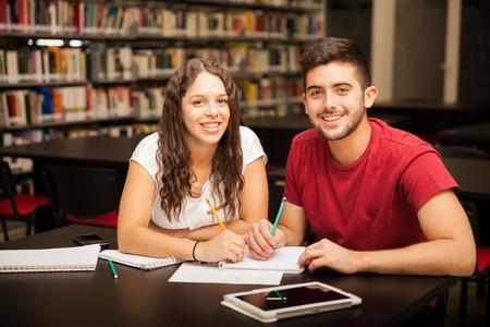 library: Retrato de una joven morena linda con el pelo rizado que estudia con su novio en la biblioteca y sonriente