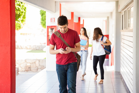 corridors: Young man using his cell phone for texting while walking on a school hallway Stock Photo