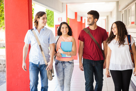 hispanic students: Attractive Hispanic college students walking together and talking on a school hallway