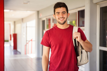 Portrait of a Hispanic college student carrying a backpack and standing in a school hallway