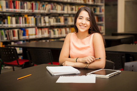 hispanic students: Cute young Hispanic woman doing some homework at the school library and smiling Stock Photo