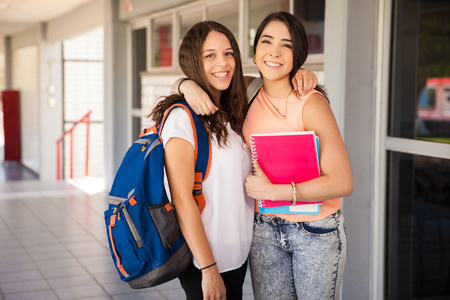 hispanic students: Portrait of a couple of gorgeous Hispanic female friends hanging out at school