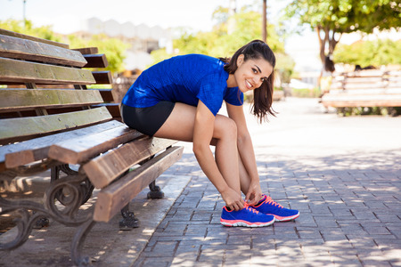 getting ready: Beautiful young Hispanic woman tying her shoes and getting ready for a run at the park