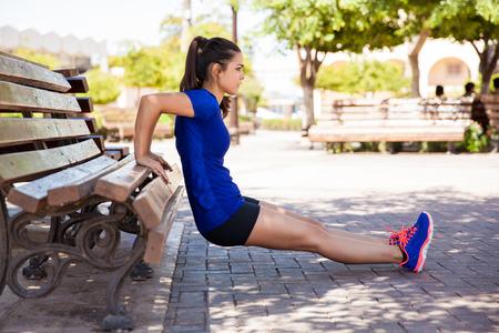 gimnasio mujeres: Vista de perfil de un atleta de sexo femenino que hace algunas ca�das de tr�ceps en un banco del parque