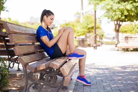 pretty: Pretty young woman in sporty outfit using a smartphone and listening to music while sitting on a park bench