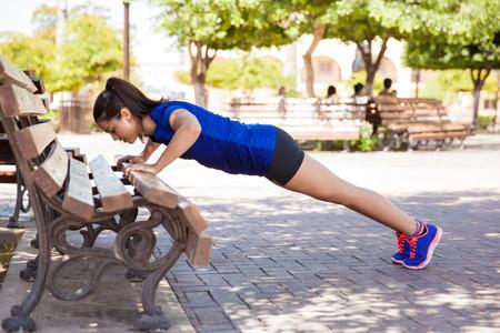 banc de parc: Vue de profil d'une jeune femme faisant push ups sur un banc de parc